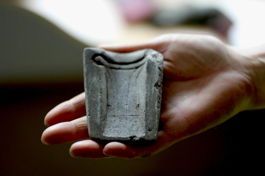 Et sjeldent funn: Denne klebersteinsformen har antagelig blitt brukt som støpeform for de sjeldne bronseøksene. Kanskje ligger også den andre delen av formen et sted på Lundamo.